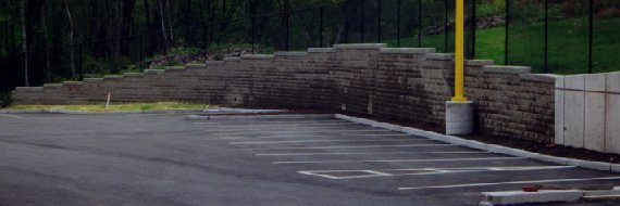 Segmental retaining wall abutting concrete panels